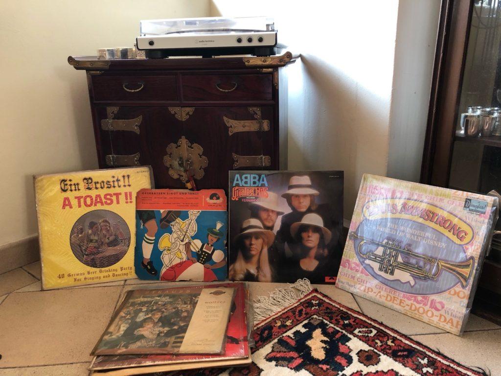Verschiedene Schallplatten inkl. Abba vor einer Kommode auf der ein Schallplattenspieler steht.