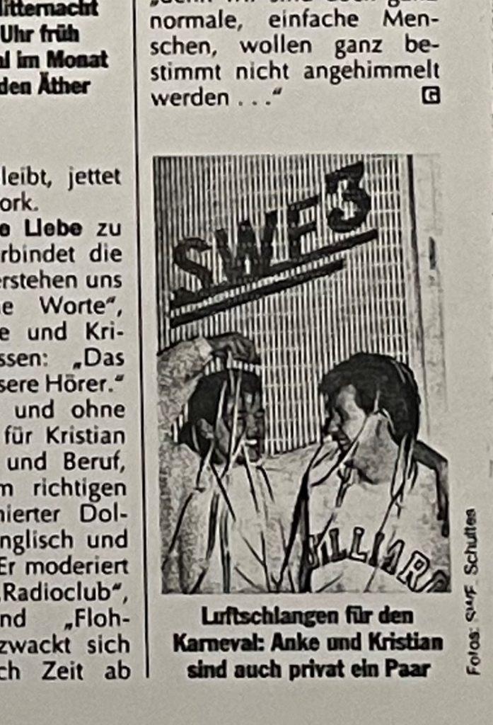 """Zeitungsausschnitt. Ein Bild auf dem Anke und Kristian schemenhaft zu erkennen sind mit der Bildunterschrift """"Luftschlangen für den Karneval: Anke und Kristian sind auch privat ein Paar"""""""